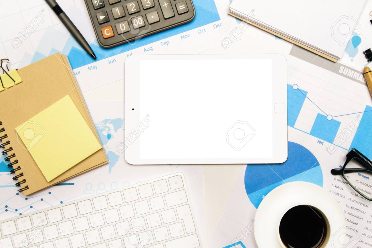 hight resolution of stock photo topview of tabletop with blank white tablet keyboard spiral notepad and other office tools on business charts mock up