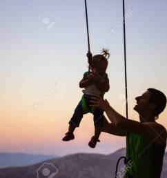 rock climber giving a swing to his little daughter in safety harness hanging on rope stock [ 1300 x 864 Pixel ]