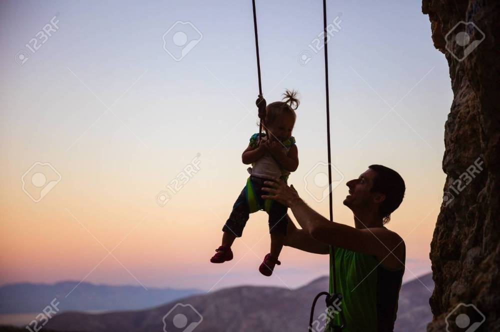 medium resolution of rock climber giving a swing to his little daughter in safety harness hanging on rope stock