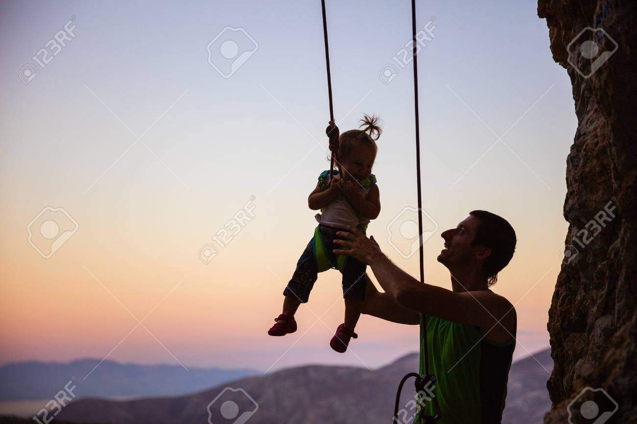 hight resolution of rock climber giving a swing to his little daughter in safety harness hanging on rope stock