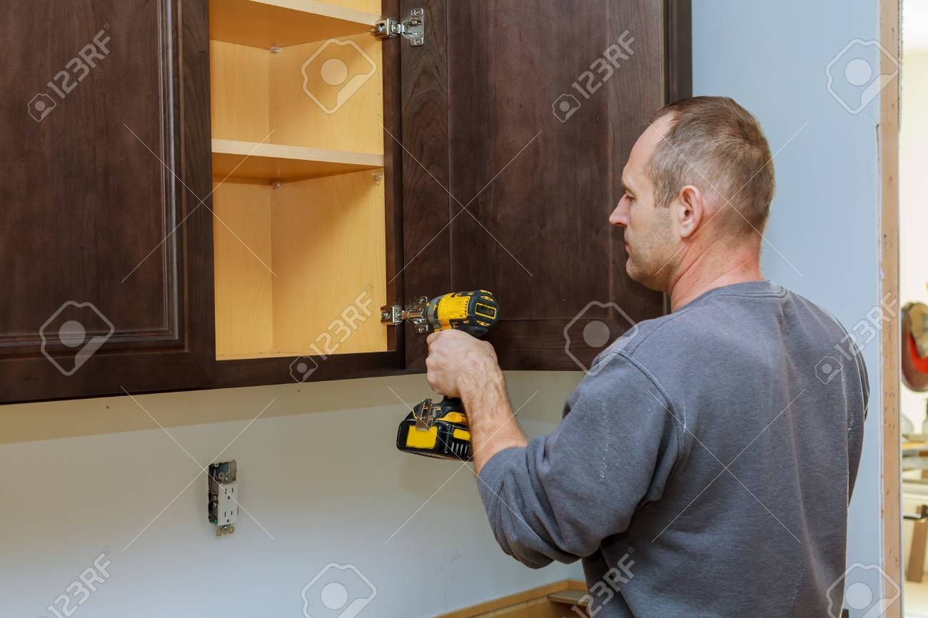 Handyman Fixing Kitchen's Cabinet With Screwdriver Adjusting Stock