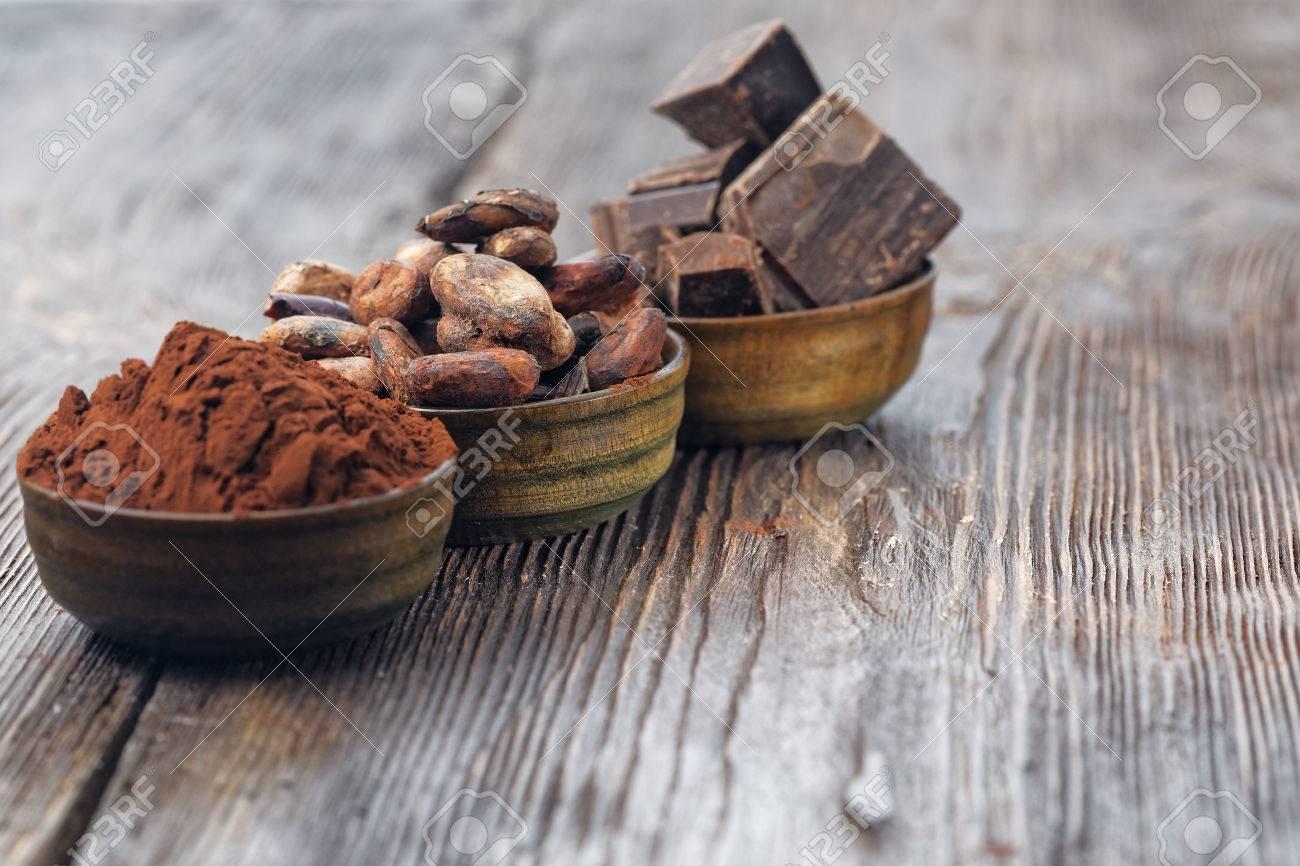 morceaux de chocolat noir la poudre de cacao et les feves de cacao sur une table en bois banque d images et photos libres de droits image 54882584