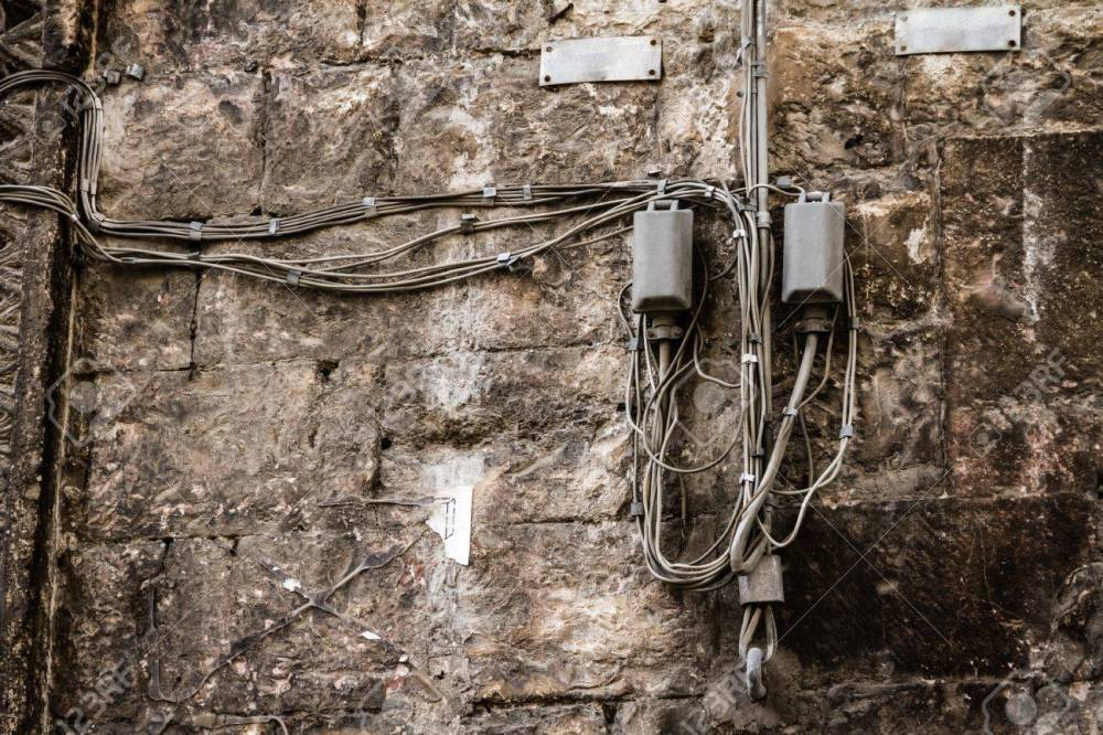 medium resolution of messy telephone or electricity cables hanged on a weathered wall stock photo 20564400