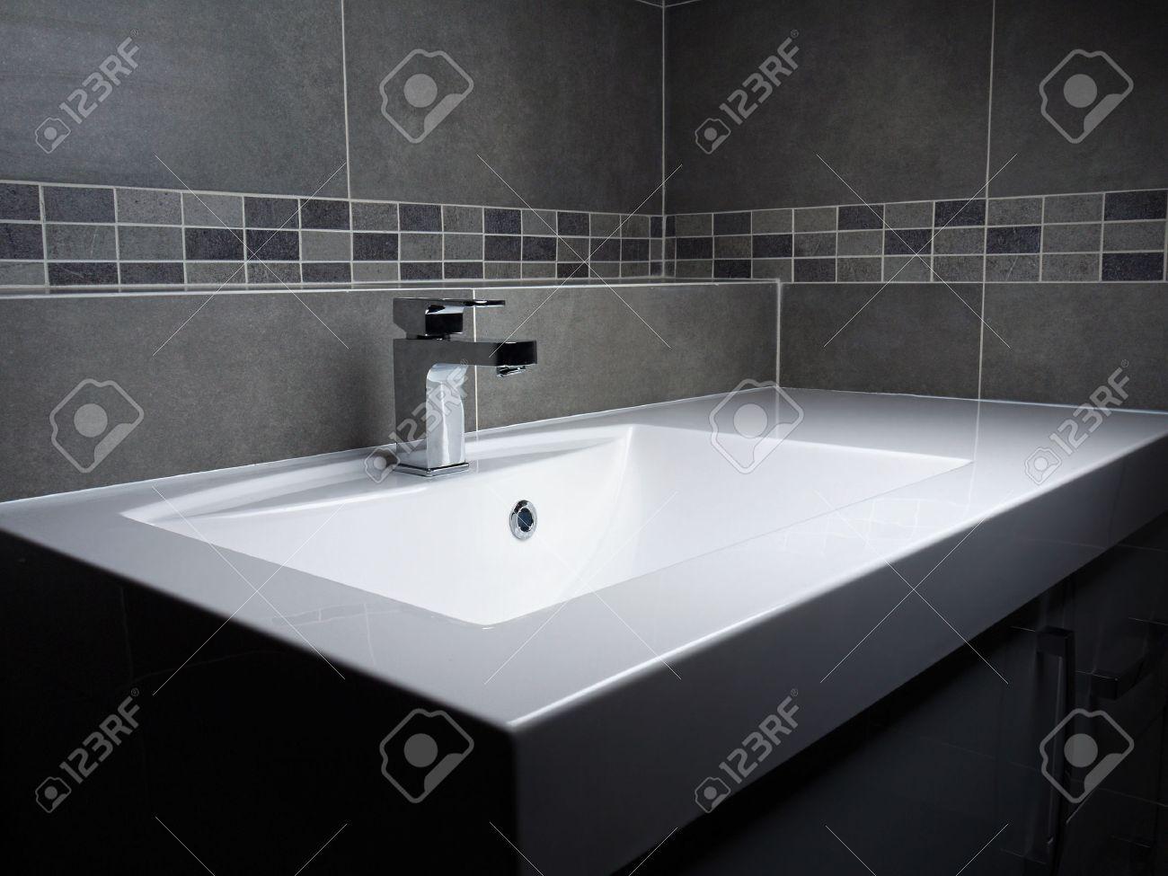 salle de bains moderne lavabo avec robinet chrome et de carrelage gris