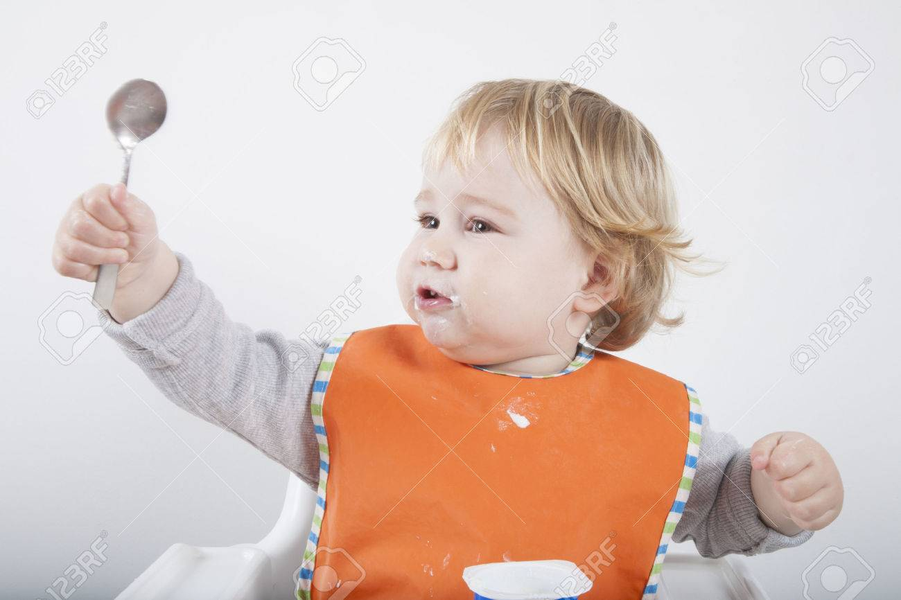 age for high chair isle of palms beach company blonde caucasian baby seventeen month orange bib grey sweater on white with spoon