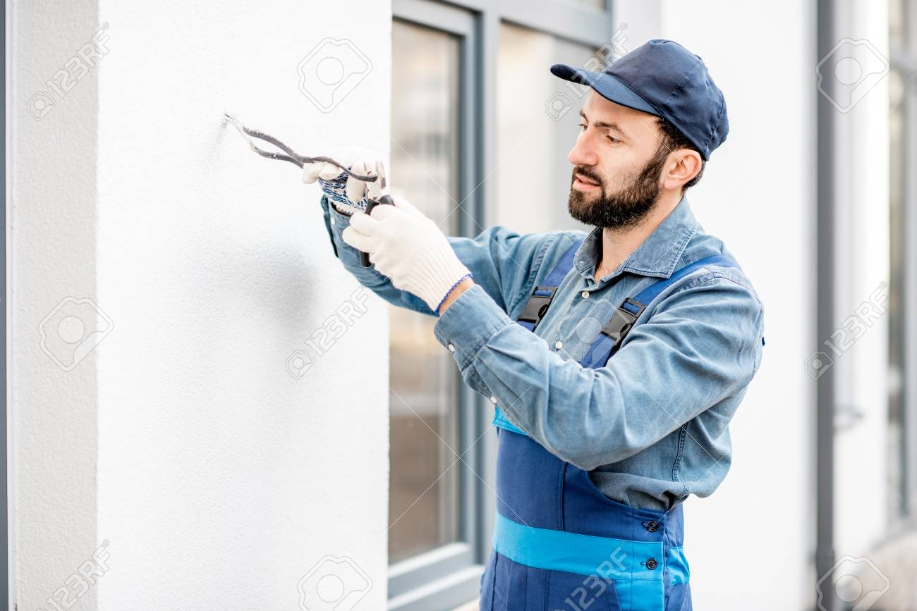 hight resolution of builder mounting electric wiring on the building facade for outdoor lighting stock photo 112134069