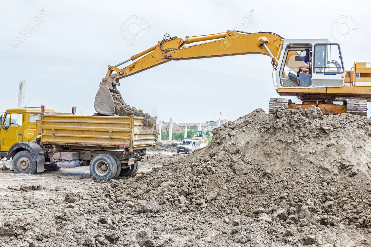 hight resolution of stock photo yellow excavator is filling a dump truck with soil at construction site project in progress