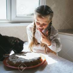 Cats In The Kitchen Discounted Appliances Child Girl Feeding A Black Cat Stock Photo Picture 69643142