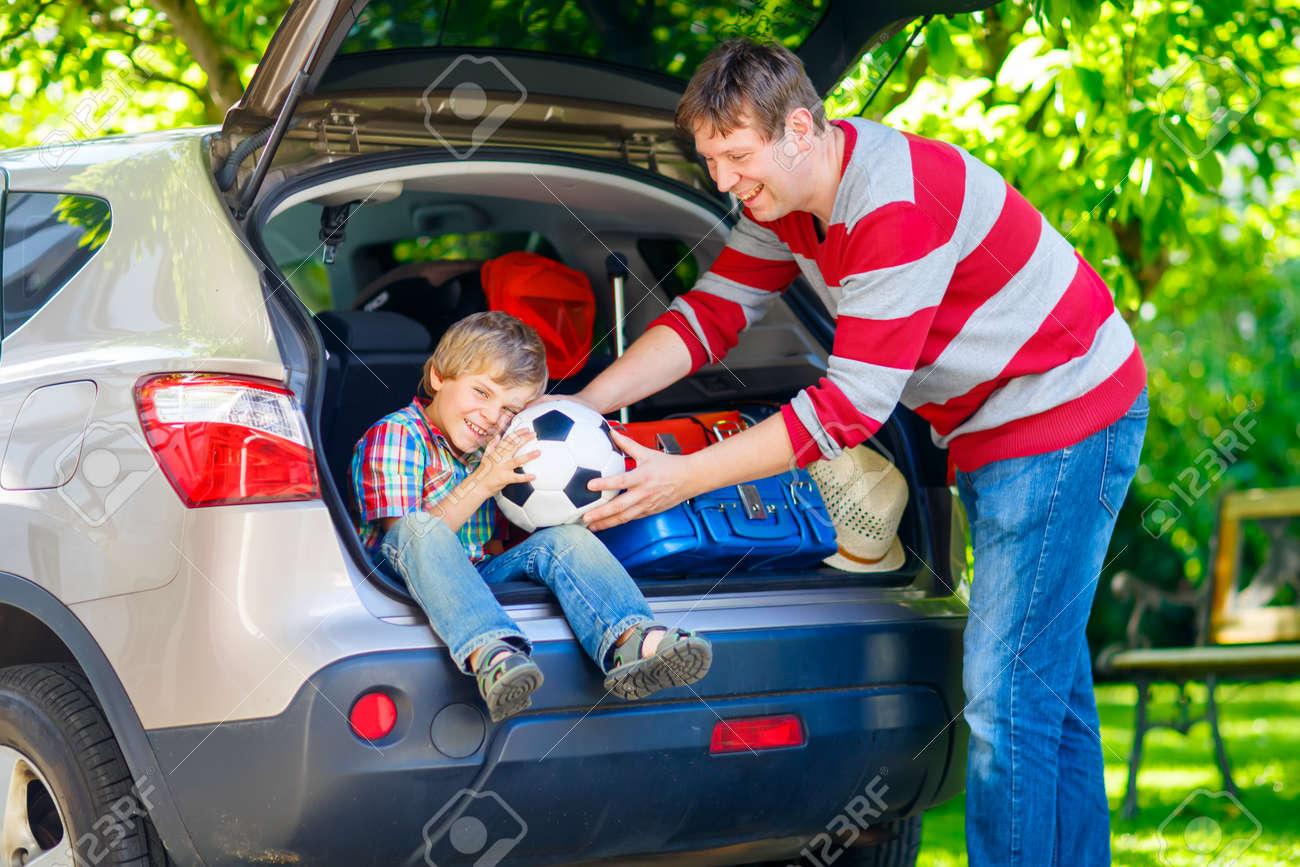 adorable petit enfant garcon assis dans un coffre de voiture juste avant de partir pour les vacances d ete papa d emballage des valises happy family