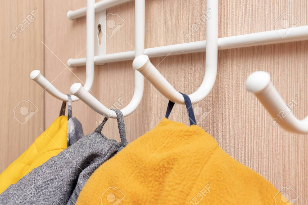 winter outerwear coat hanging on a hook of a coat rack in hallway