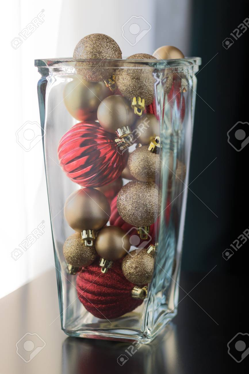 https www 123rf com photo 91667351 red and gold christmas ball ornaments are placed in a glass jar as a table decorative piece as seen html