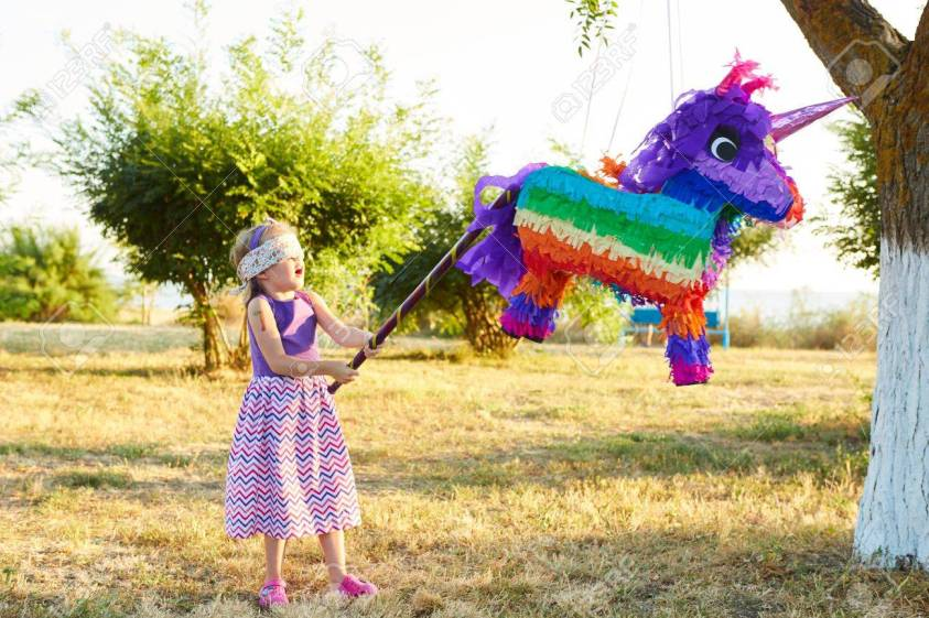 Young Girl At An Outdoor Party Hitting A Pinata. Celebrating ...