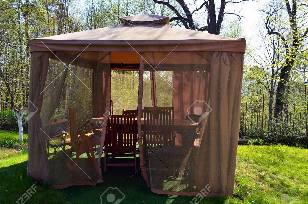 kiosque tonnelle avec moustiquaire arbor proteger net bancs de repos et des tables des chaises pres du jardin ferme