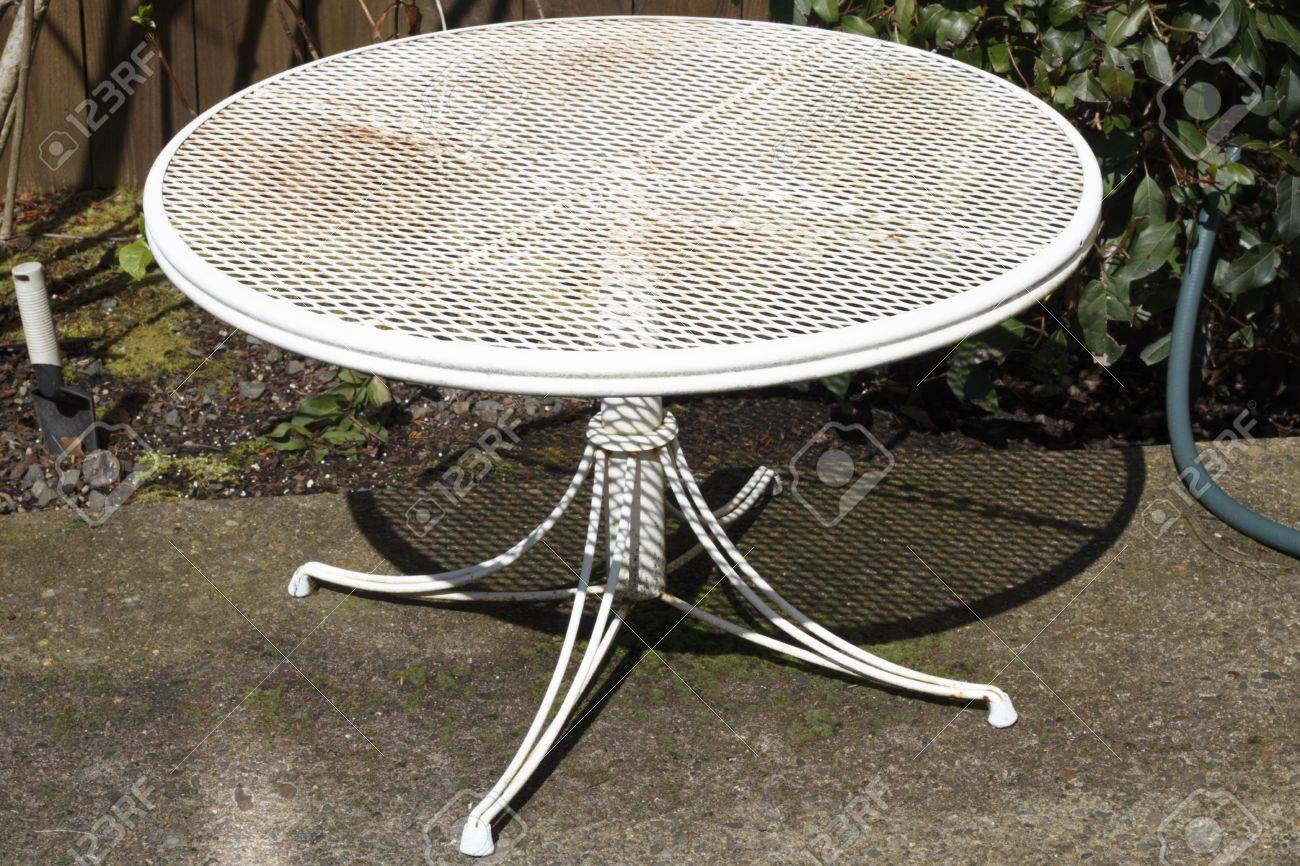 small round metal patio table painted white aged with dirt and