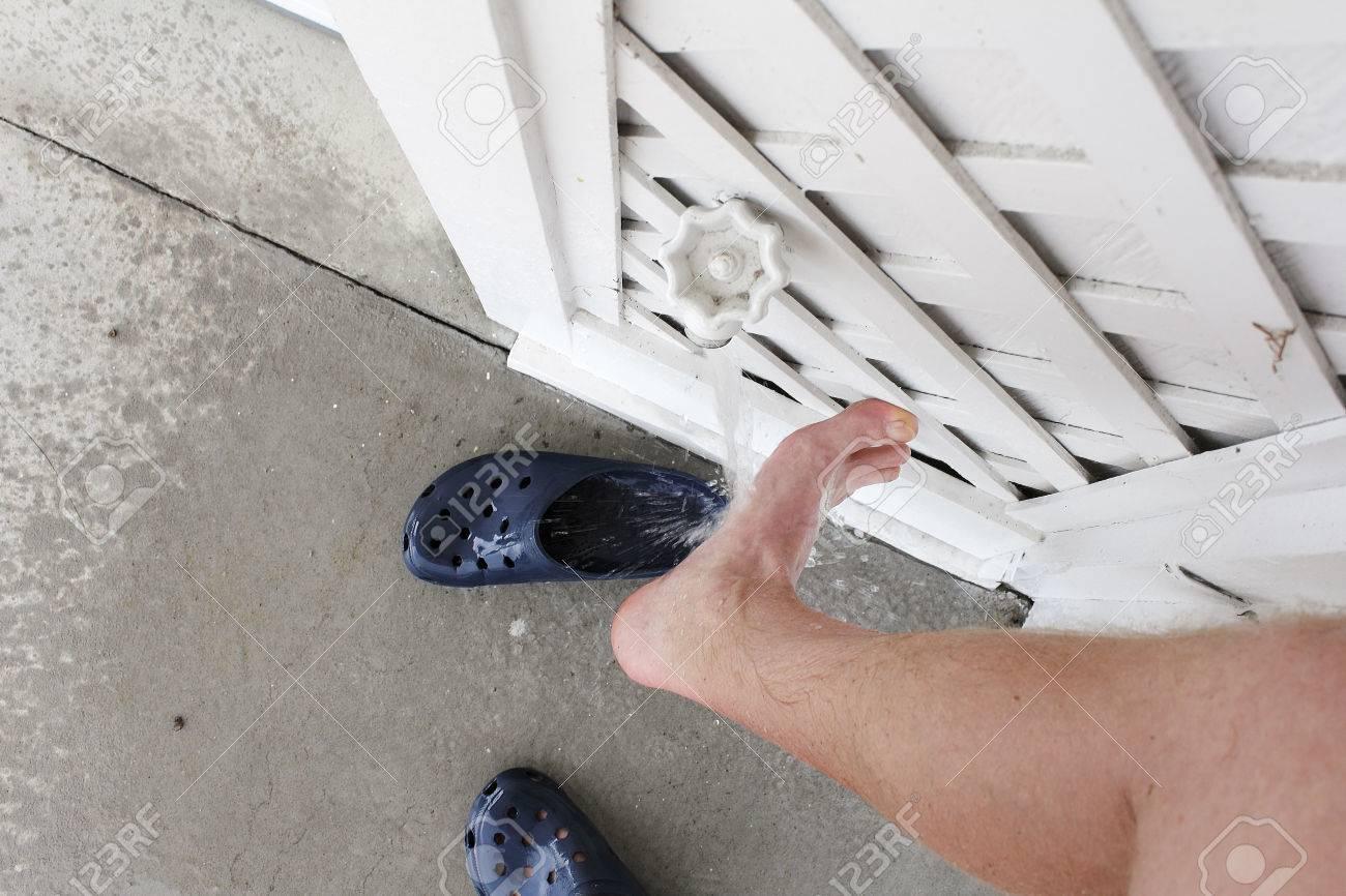 pied etant rince du sable de plage avec de l eau a l exterieur a partir d un robinet de la maison un pied droit agrandi male etant nettoye de sable avec un jet d eau