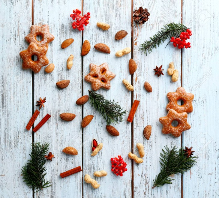 Cookies with nuts and sprigs of Christmas tree on color wooden background  Stock Photo - 99653877