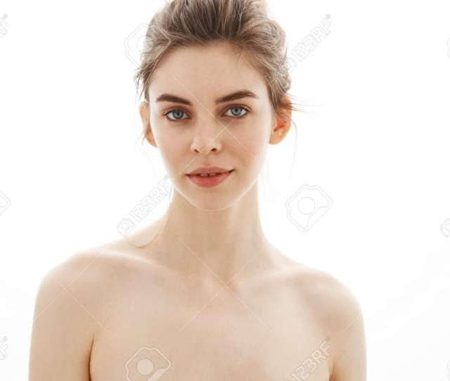 Portrait Of Young Beautiful Tender Naked Girl With Bun Looking At Camera Over White Background
