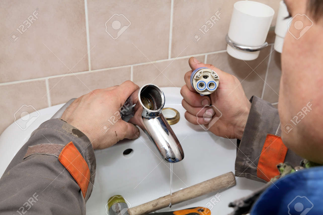 Plumber Fixing Water Tap Ceramic Cartridge Valve In A Bathroom Stock Photo Picture And Royalty Free Image Image 18624528