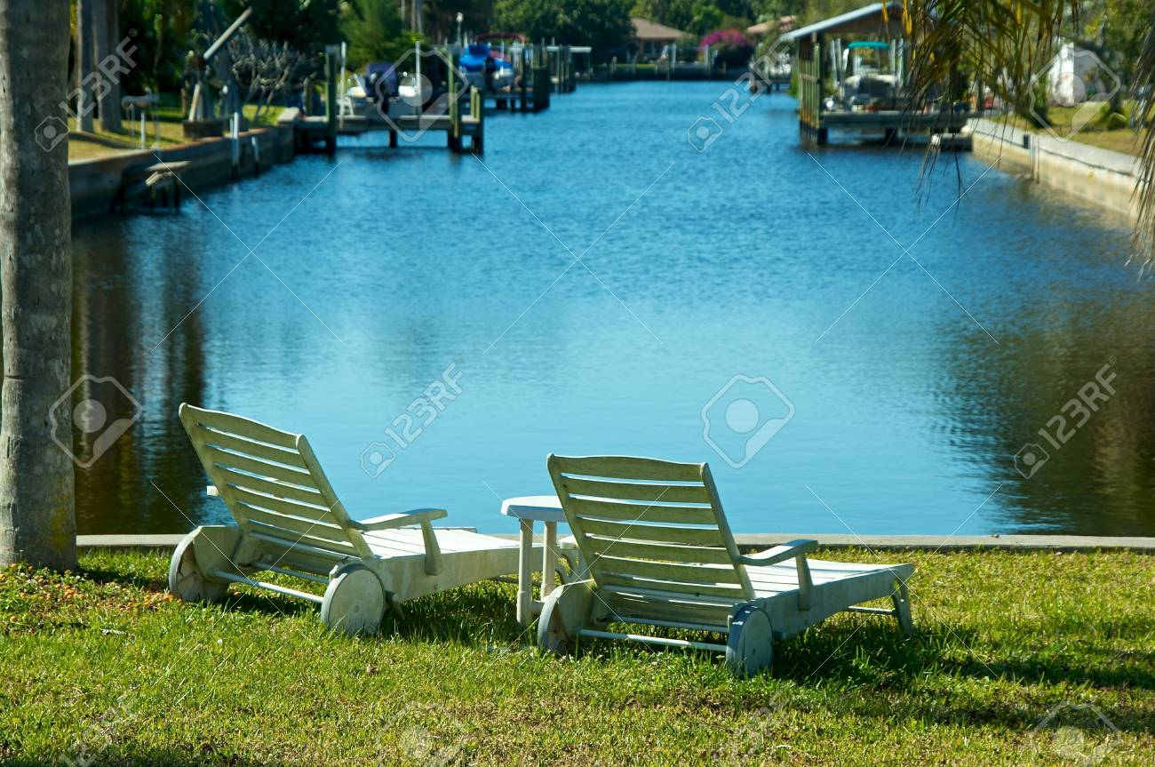 Outside Lounge Chairs Two White Outside Lounge Chairs Are Sitting By The Water At The