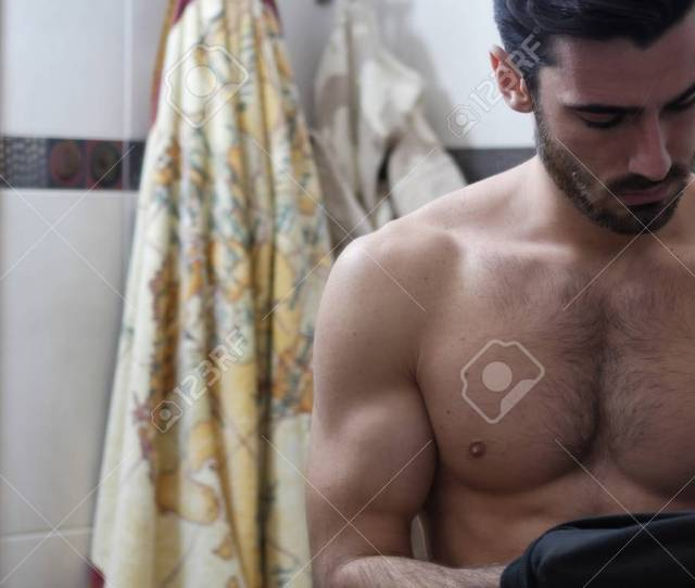 Attractive Muscular Young Man Dressing Putting On Black T Shirt In Bathroom Hiding