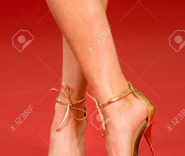 Sexy Legs Of A Woman Wearing Golden High Heels Shoes On A Red Carpet Stock