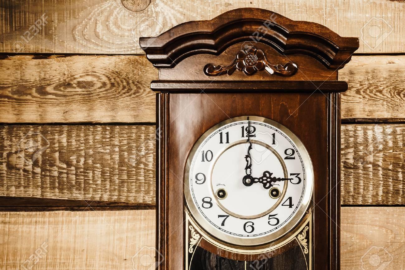 horloge ancienne et grande accroche sur un mur en bois