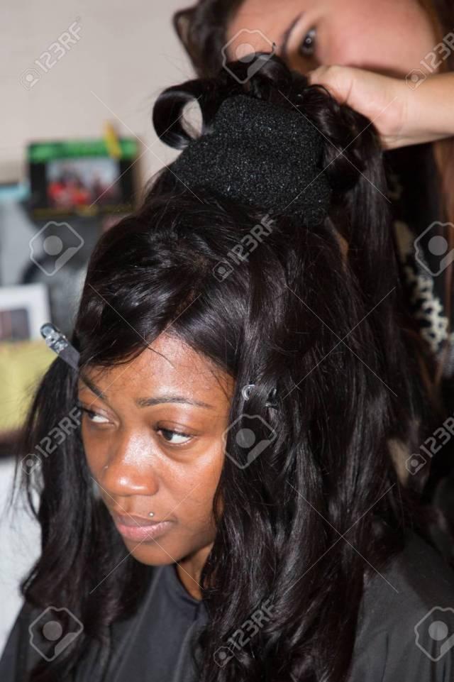 professional hair stylist makes black bride wedding hairstyle..