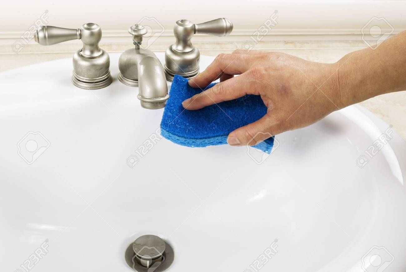 hand with sponge cleaning bathroom sink faucet