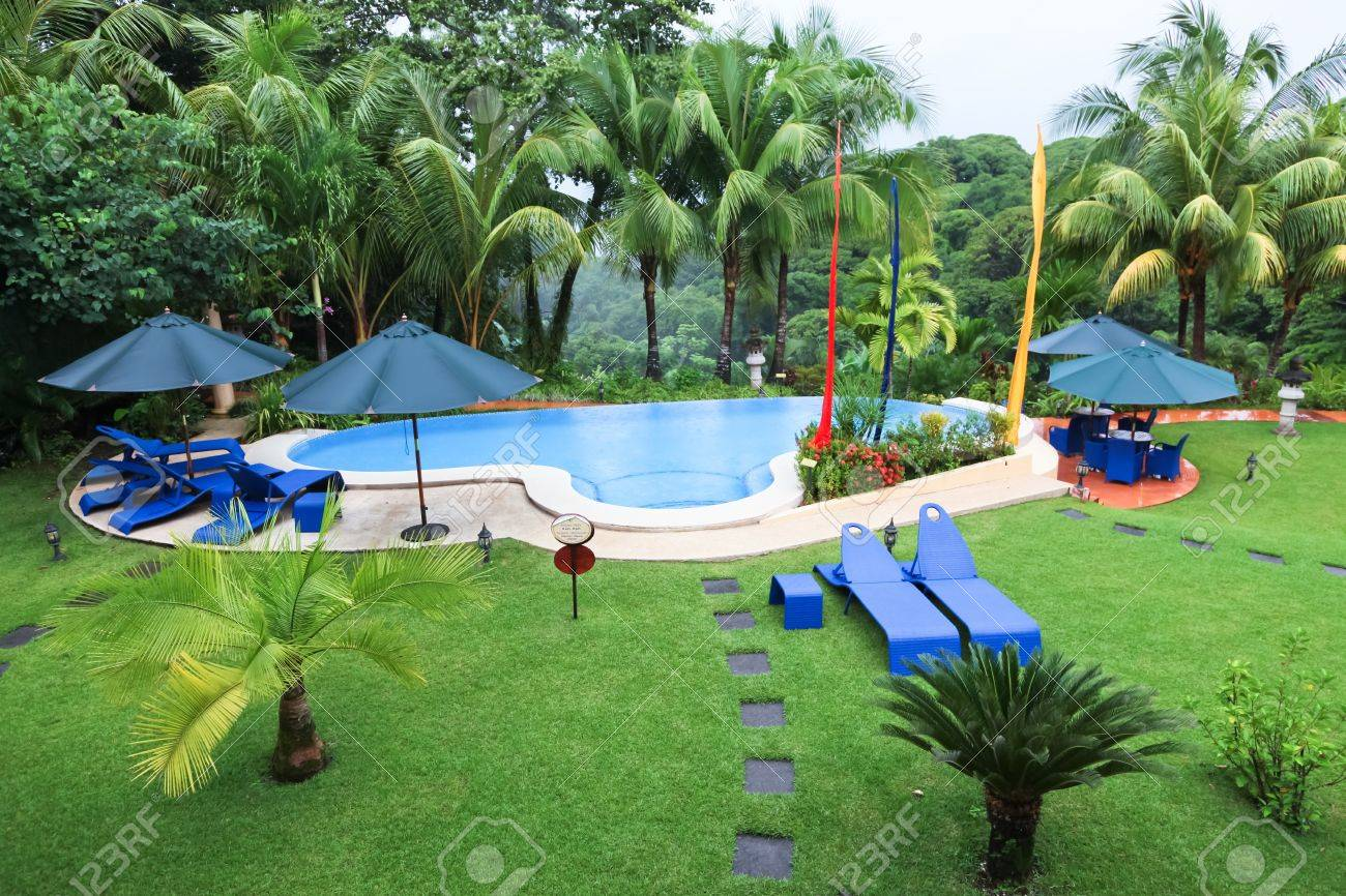 a swimming pool and patio furniture in the rain surrounded by