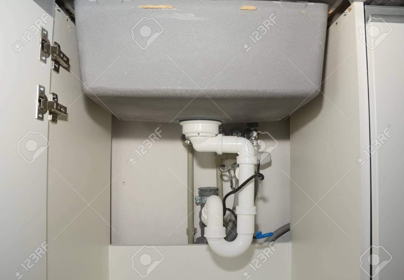 close up on ceramic kitchen sink installation with sink drain