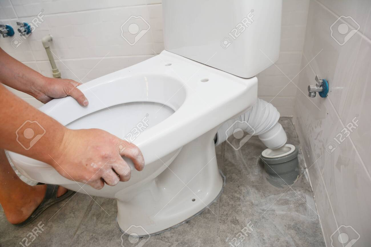 Repairman Hands Installing Flush Toilet Toilet Bowl In The Bathroom Stock Photo Picture And Royalty Free Image Image 134866097