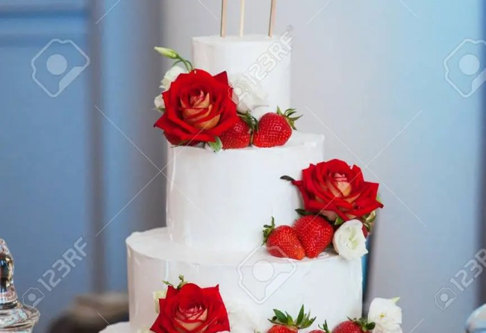 Four Layer White Wedding Cake With Red Roses And Strawberries