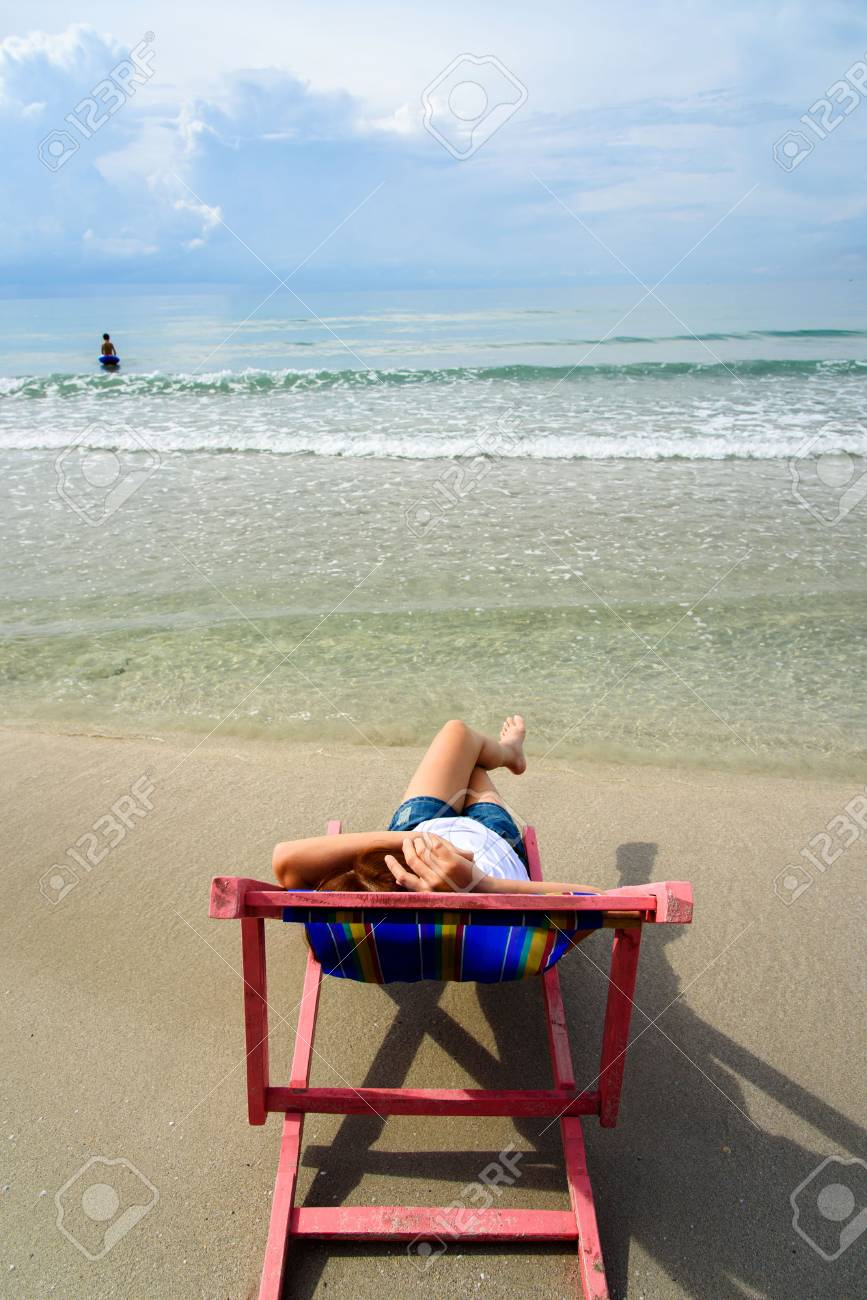 pink beach chair gaming with wheels woman lay on at the close of sea water stock photo