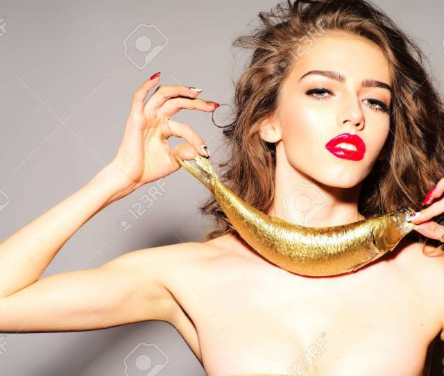 Inviting Young Naked Woman With Curly Hair Holding Golden Fish As Necklace Looking Forward Standing On
