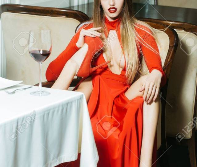 Glamour Sexy Flexible Young Woman With Long Blonde Hair Sitting In Restaurant Holding Wine Glass In