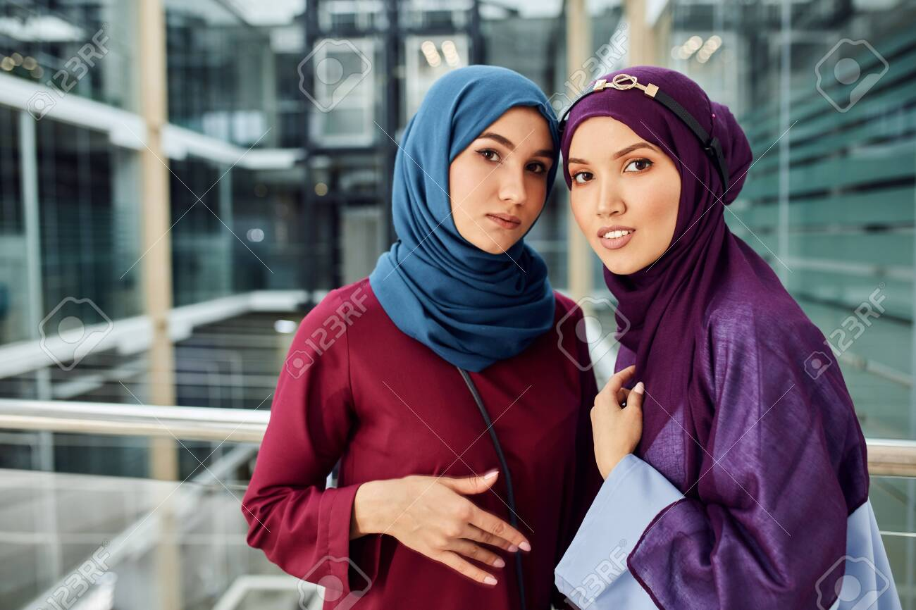 It makes me realize that true and meaningful. Couple Of Muslim Caucasian 20s Girlfriends With Hijab Or Islamic Head Scarfs And Islamic Traditional Clothes Looking At Camera Standing In Modern Glass Business Centre Stock Photo Picture And Royalty Free Image