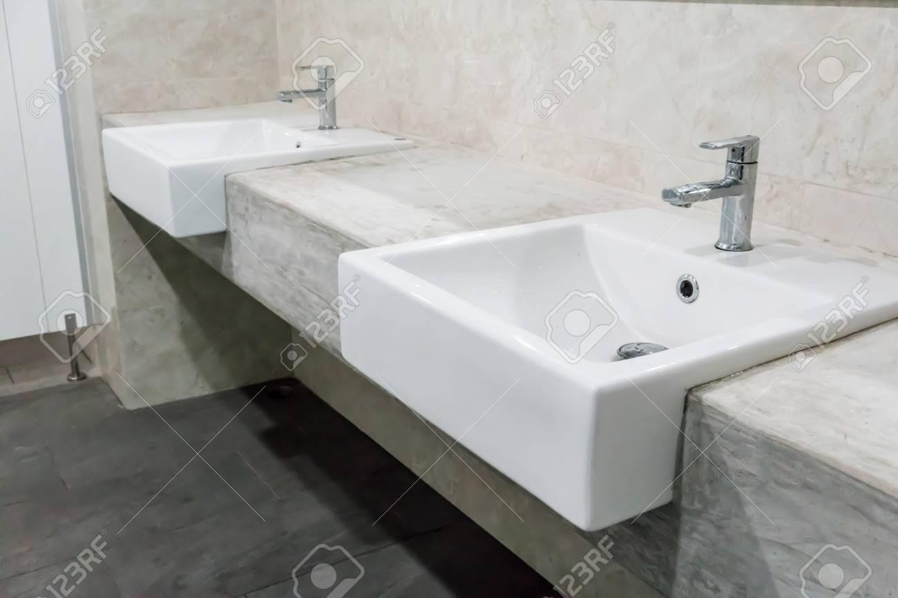 minimal style bathroom with two sinks and granite vanity top