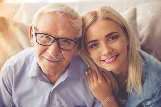 Portrait Of Handsome Old Man And Beautiful Young Girl Hugging Looking At Camera And Smiling