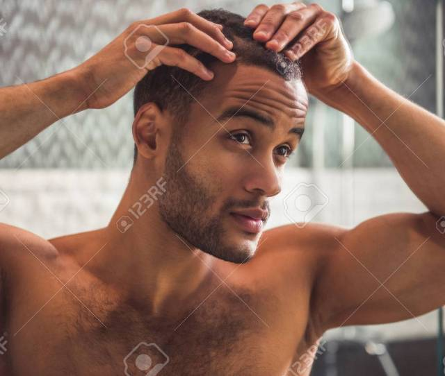 Handsome Naked Afro American Man Is Examining His Hair While Looking Into The Mirror In Bathroom