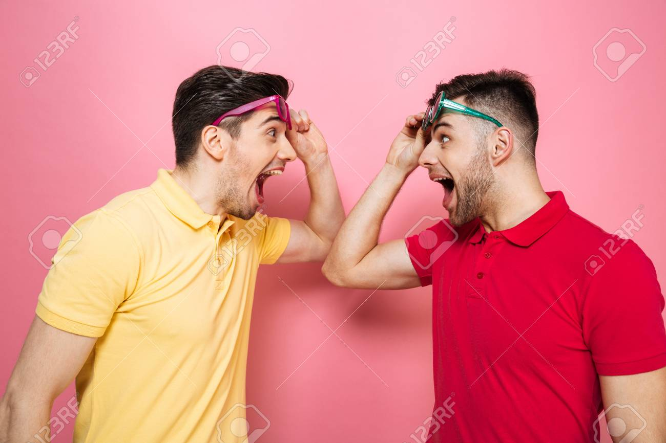 Portrait Of A Surprised Gay Male Couple In Sunglasses Looking At Each Other Isolated Over Pink