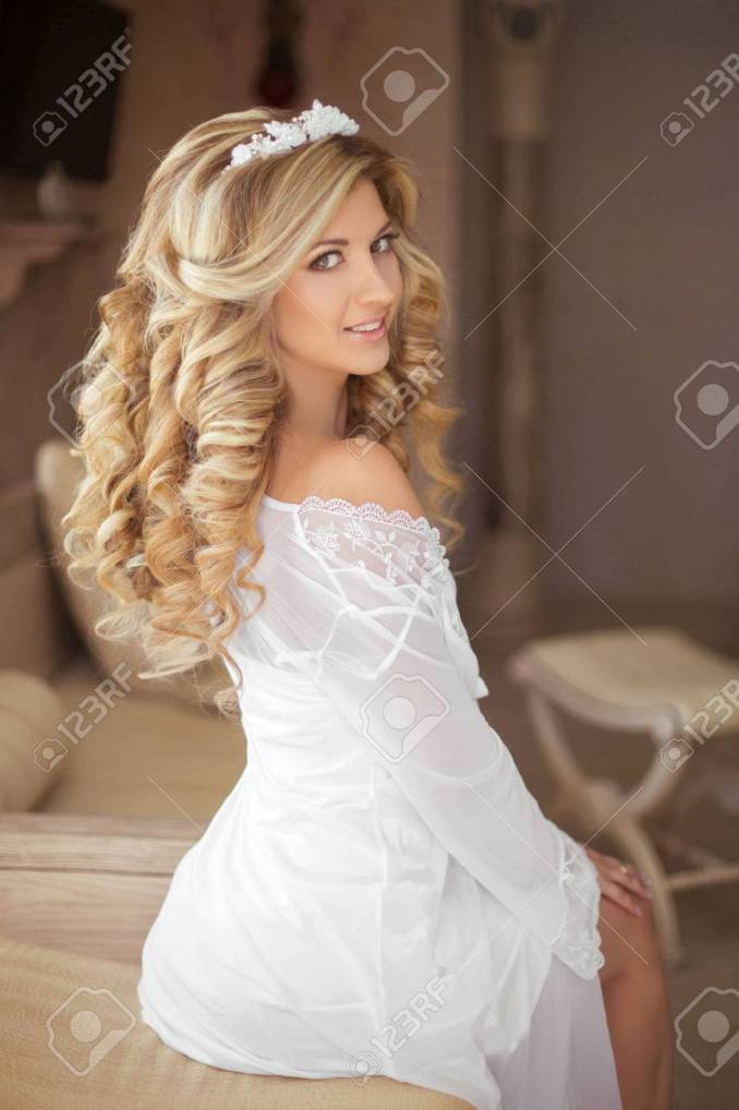 healthy hair. beautiful smiling girl bride with long blonde curly..