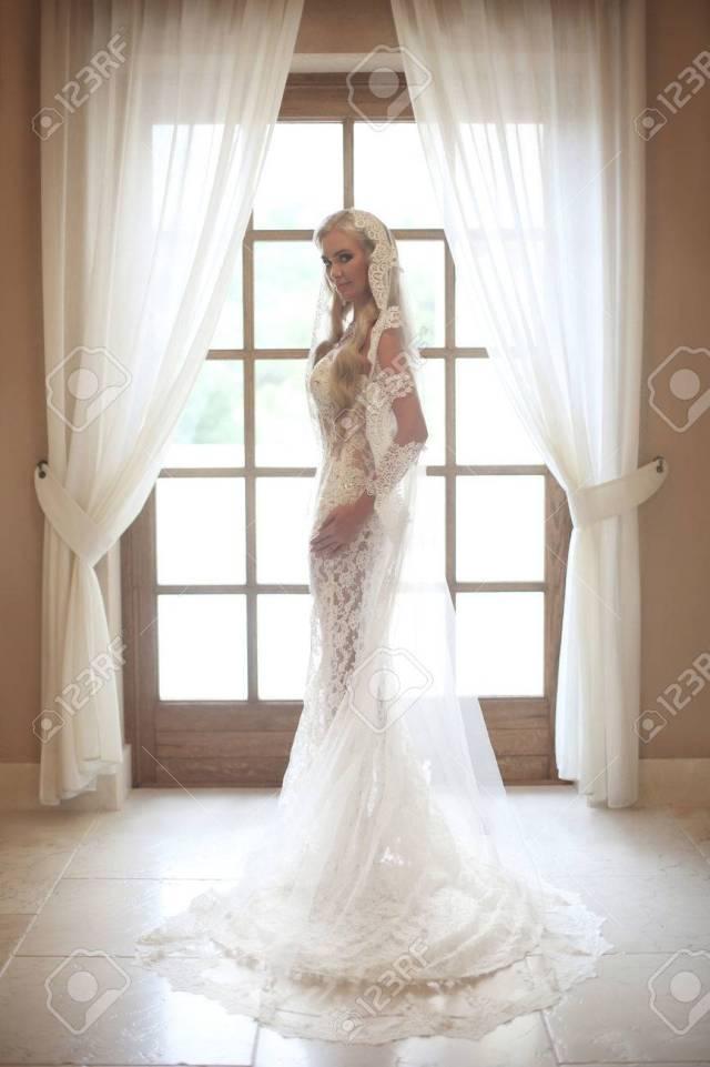 beautiful bride in wedding dress with long bridal veil posing..