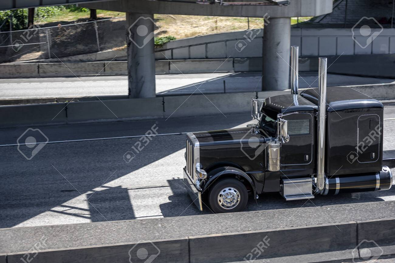 black big rig american bonnet semi truck with high exhaust pipes