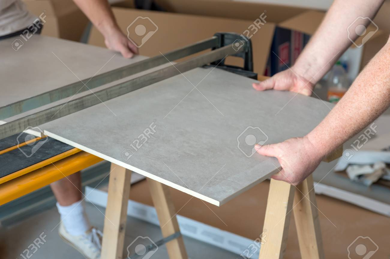 workers cutting ceramic floor tiles tile with tile cutter stock photo picture and royalty free image image 106610887