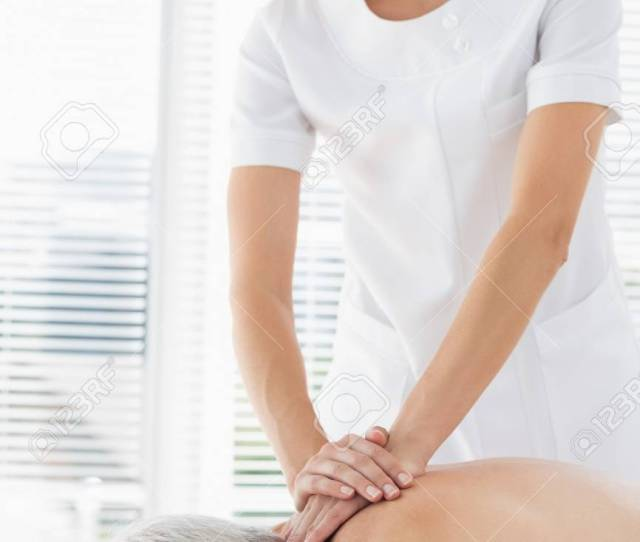 Female Massage Therapist Massaging Back Of Senior Man In Clinic Stock Photo 27119916