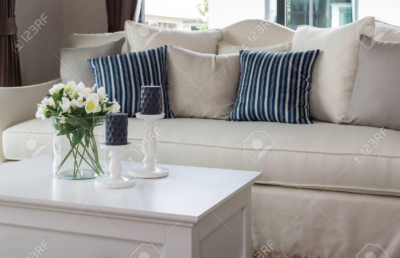 salon moderne avec vase de verre et rangee de coussins sur un canape