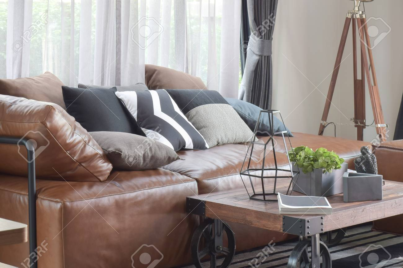 wood center table with wheel and light brown leather sofa in