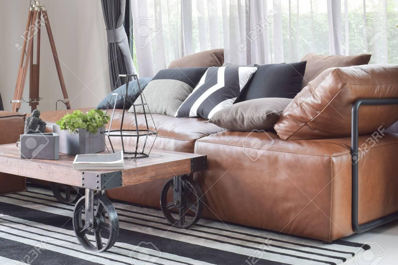 table de centre en bois avec roulette et canape en cuir marron clair en decoration de style industriel
