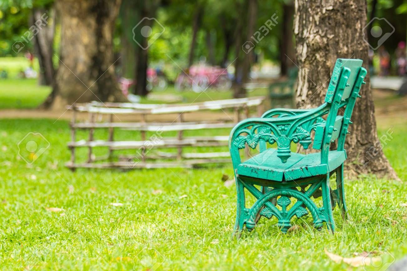 This cute photography chair is made of green wrought iron. green chair in the public park with people riding bicycle on