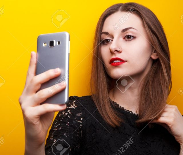 Selfie Sexy Girl Doing Selfie On A Yellow Background Stock Photo